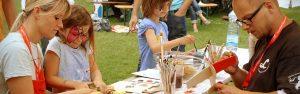 Sommerfest - ehrenamtliche Mitarbeiter malen mit Kindern